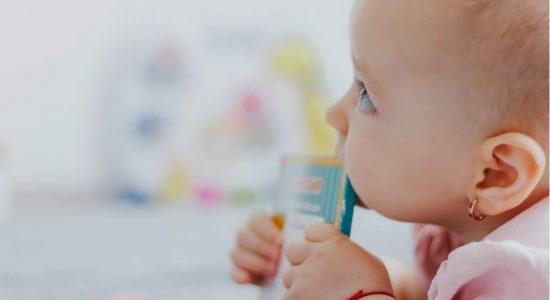 Bébé en pleine poussée dentaire qui mâchouille un objet
